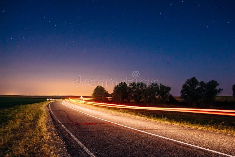 Los rastros de las linternas del coche en una noche ajardinan con un unde del camino fotos de archivo libres de regalías