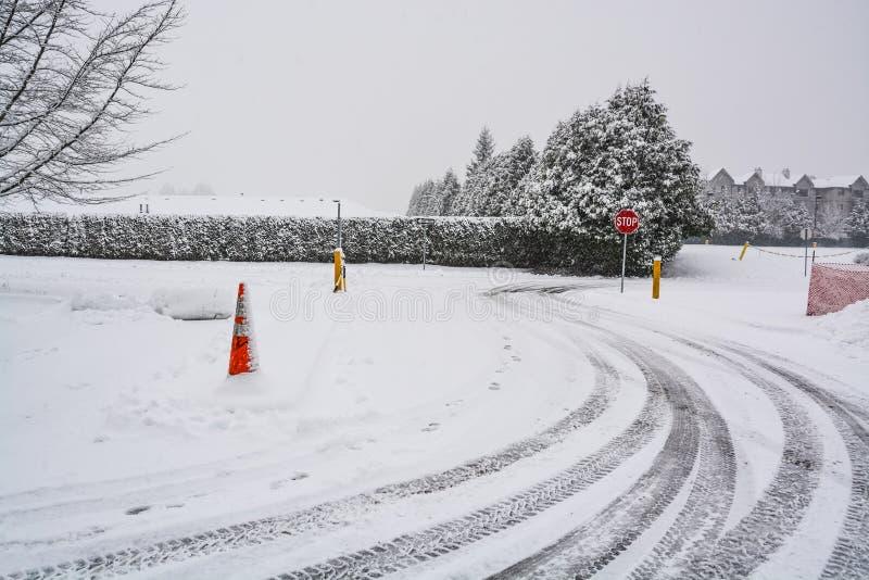 Los rastros de los neumáticos del invierno en vuelta del camino nevoso con la parada firman en frente foto de archivo libre de regalías