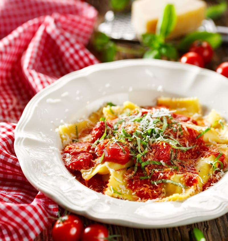 Los raviolis remataron con la salsa de tomate, el queso del padano del grana y la albahaca fresca imágenes de archivo libres de regalías
