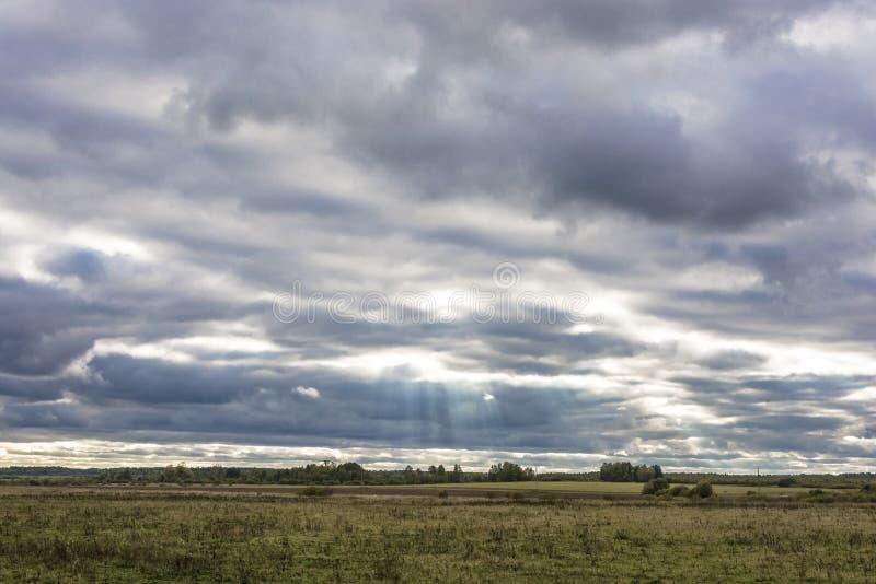 Los rayos brillantes del sol perforan a través de las nubes cubiertas por la tarde del otoño foto de archivo