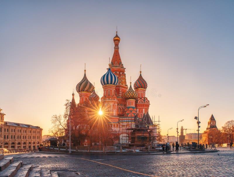 Los rayos de la catedral de la albahaca del sol y del St Monumento a Minin y a Pozharsky bajo reconstrucción fotografía de archivo libre de regalías