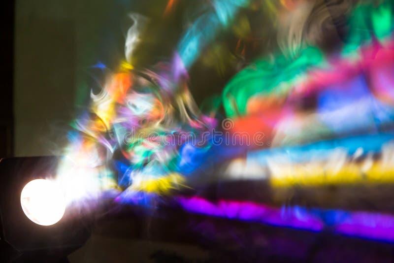 Los rayos de la luz coloreados del reflector a través del humo Un funcionamiento de teatro, un concierto o un disco Reflector del fotos de archivo
