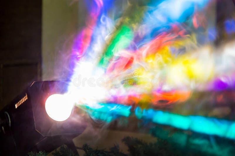 Los rayos de la luz coloreados del reflector a través del humo Un funcionamiento de teatro, un concierto o un disco Reflector del foto de archivo