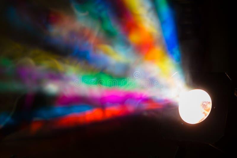 Los rayos de la luz coloreados del reflector a través del humo Un funcionamiento de teatro, un concierto o un disco Reflector del foto de archivo libre de regalías
