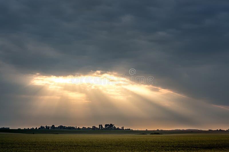 Los rayos de la luz penetran a través de las nubes gruesas durante el ascensio imagen de archivo