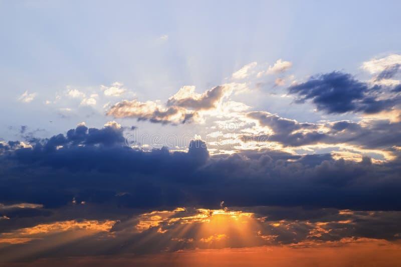 Los rayos del sol hacen su manera a través de las nubes, el cielo imagen de archivo libre de regalías