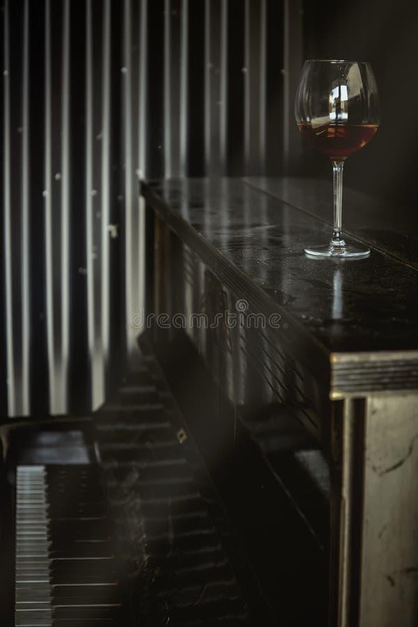Los rayos del sol iluminan un vaso de vino tinto en un piano viejo, polvoriento y rayado. Imagen de color cálido fotografía de archivo