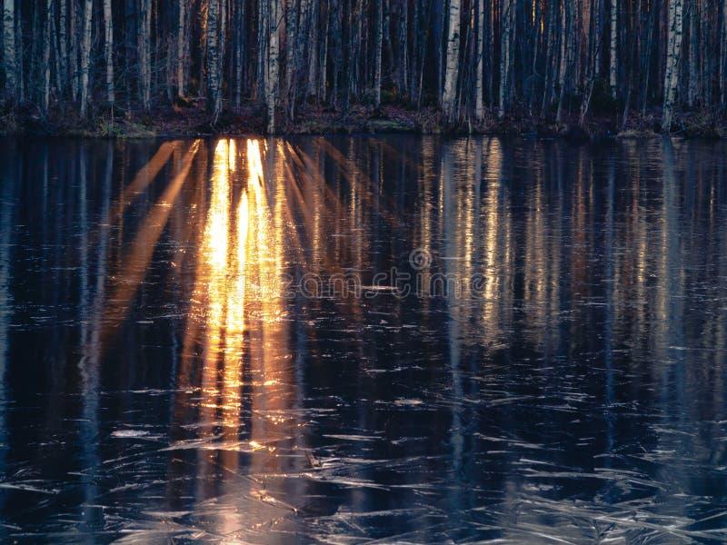 Los rayos del sol poniente se reflejan en el agua de río que comenzó a ser cubierta con el primer hielo imagenes de archivo