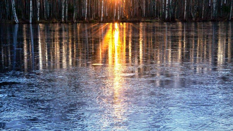 Los rayos del sol poniente se reflejan en el agua de río que comenzó a ser cubierta con el primer hielo foto de archivo