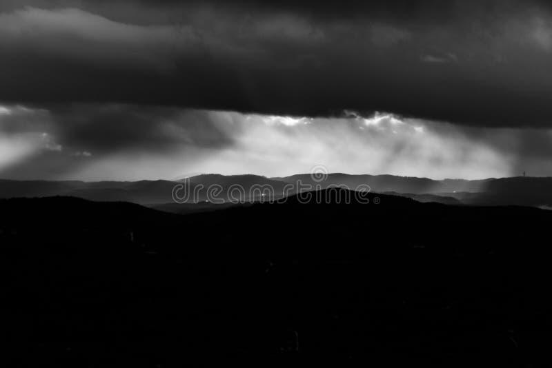 Los rayos del sol se abalanzan sobre las montañas bajo las nubes húmedas foto de archivo