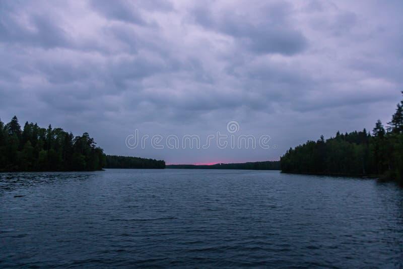 Los rayos pasados del sol tarde en la noche sobre un pequeño lago del bosque en Karelia Rusia imagen de archivo
