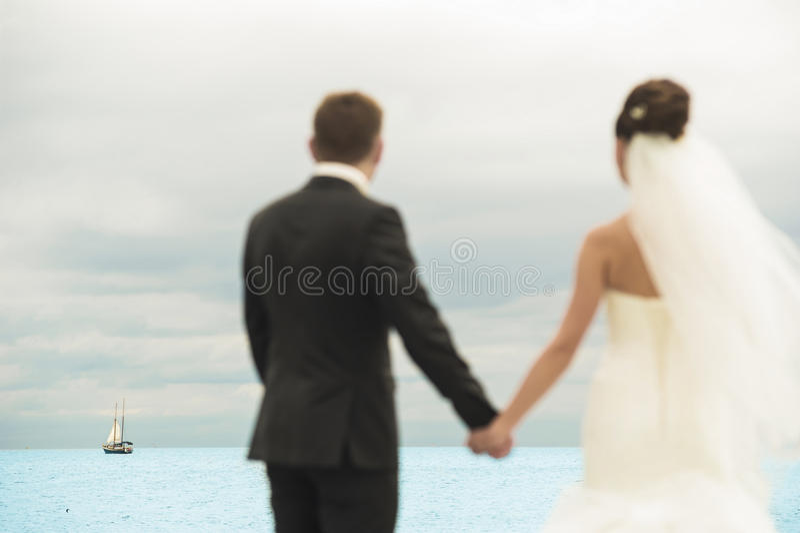 Los recienes casados agradables están haciendo una pausa la costa imagen de archivo libre de regalías
