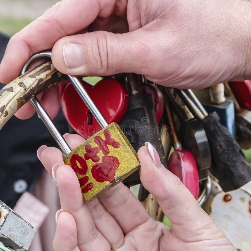 Los recienes casados cuelgan la cerradura que simboliza amor eterno en el día que se casa imagen de archivo