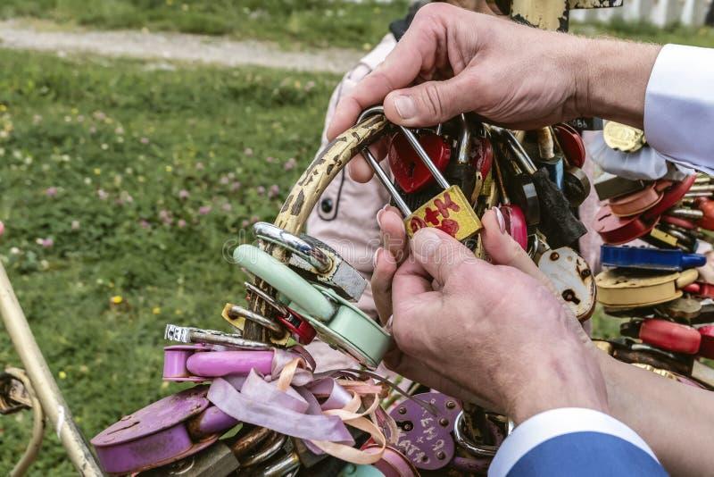 Los recienes casados cuelgan la cerradura que simboliza amor eterno en el día que se casa fotos de archivo