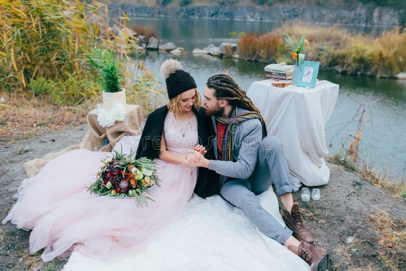 Los recienes casados elegantes de los pares son relajantes en una tela escocesa y sentarse antes de un lago La novia y el novio c fotos de archivo