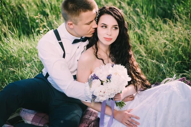 Los recienes casados en amor se están sentando en la hierba en el parque la novia y el novio sonríen y se divierten en la comida  imagen de archivo