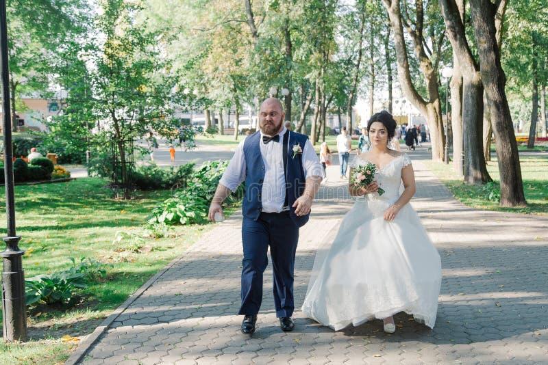 Los recienes casados están caminando en el parque y están sonriendo en uno a imagen de archivo libre de regalías