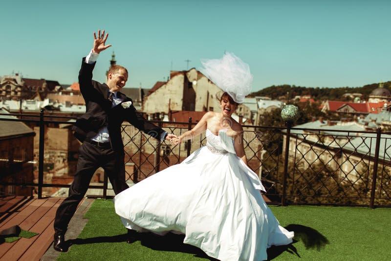 Los recienes casados felices tienen baile de la diversión en el tejado imagenes de archivo