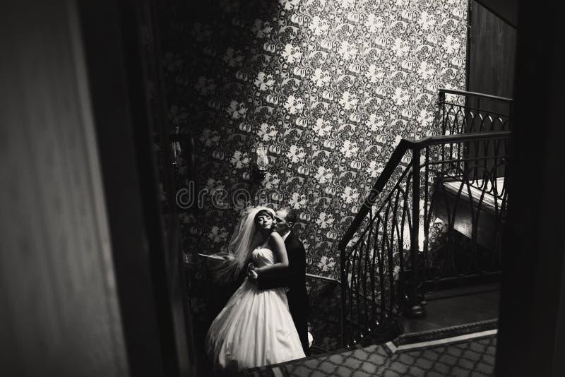 Los recienes casados imponentes abrazan en las escaleras con los ojos cerrados foto de archivo libre de regalías