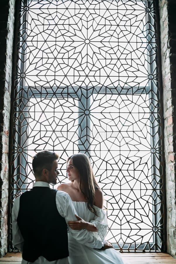 Los recienes casados jovenes hermosos están presentando en el fondo de la ventana del vintage del ornamento Discreto ilustracione fotos de archivo libres de regalías