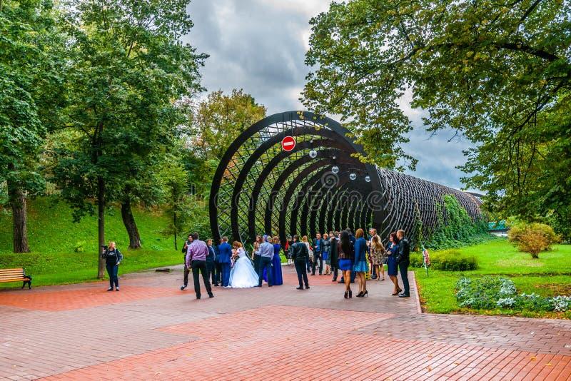 Los recienes casados llevan las fotos por la entrada el puente de Andreevsky en el MES foto de archivo libre de regalías