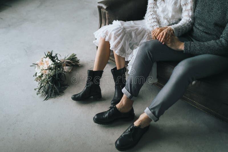Los recienes casados se sientan en casa en el sofá Piernas en las botas casuales de pares jovenes imagen de archivo