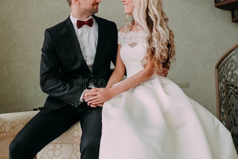 Los recienes casados sonrientes están mirando uno a con el amor que se sienta en el sofá boda imágenes de archivo libres de regalías