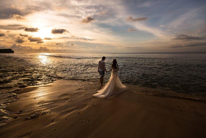 Los recienes casados van al mar en la playa fotografía de archivo