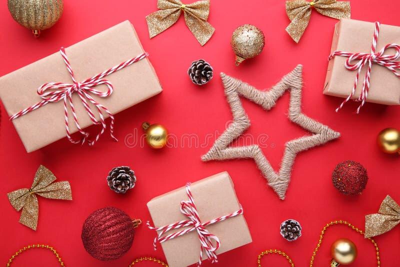 Los regalos de la Navidad presentan con las decoraciones en un fondo rojo foto de archivo libre de regalías