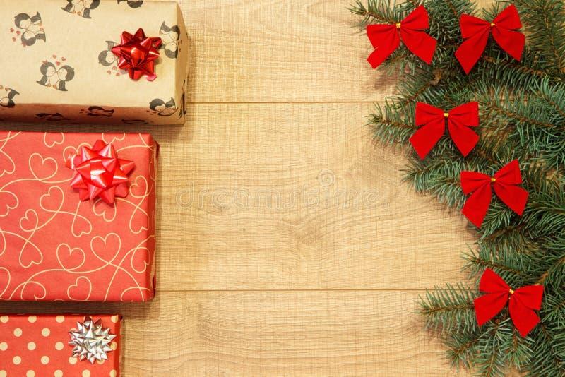 Los regalos del Año Nuevo/la Navidad en el paquete, árbol con rojo arquean en la plantilla de madera del fondo fotografía de archivo