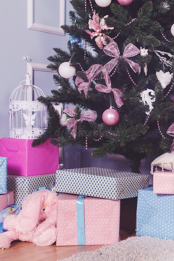 Los regalos hermosos de la Navidad debajo del árbol en Año Nuevo adornaron el interior de la casa fotos de archivo
