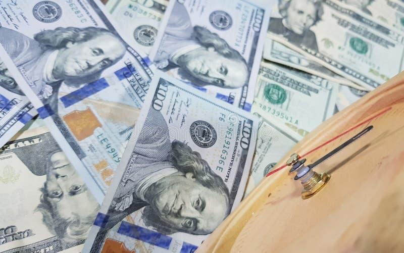Los relojes colocados contra billetes de banco del dólar toman tiempo para recibir el dinero El tiempo es oro foto de archivo