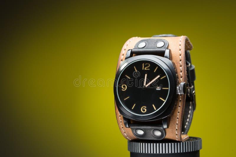 Los relojes de los hombres con la pulsera de cuero ancha imagen de archivo