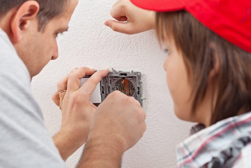 Los relojes jovenes del muchacho como su padre instalan un calcetín eléctrico de la pared imagenes de archivo
