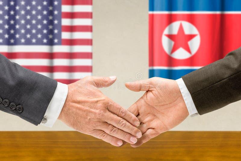 Los representantes de los E.E.U.U. y de Corea del Norte están sacudiendo las manos imagen de archivo