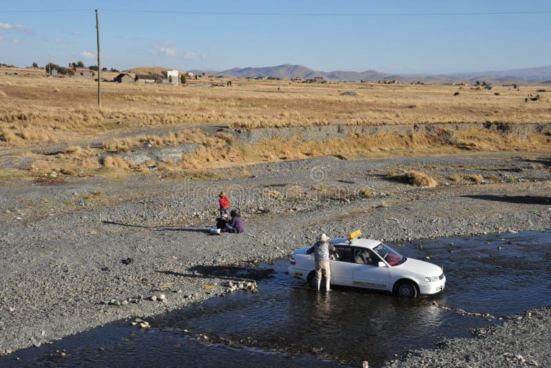 Los residentes de La Paz lavan sus coches en un río de la montaña en zona urbana imagen de archivo