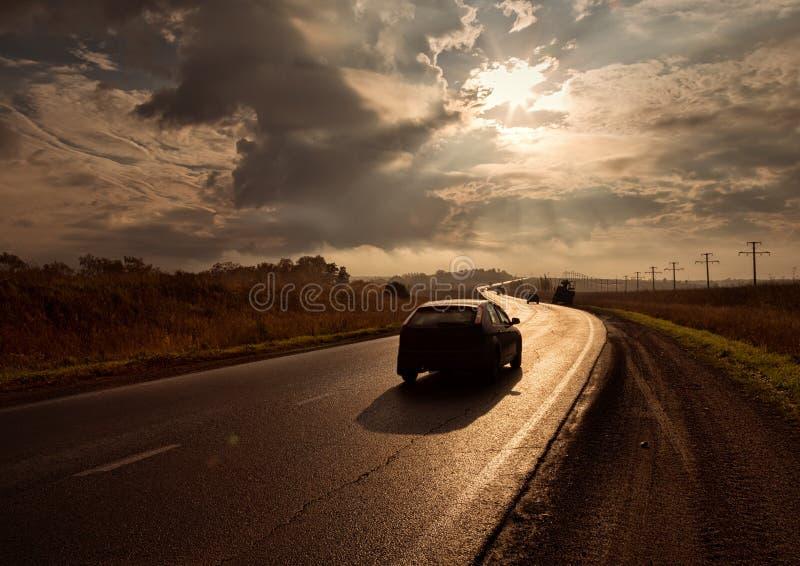 Los resplandores del camino de la puesta del sol en el sol se esfuerzan adelante imagenes de archivo