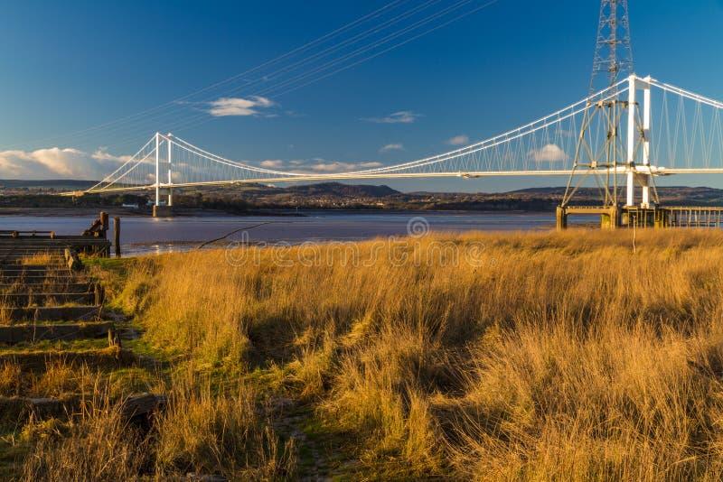 Los restos de Aust balsean el embarcadero con Severn Bridge en la distancia fotografía de archivo