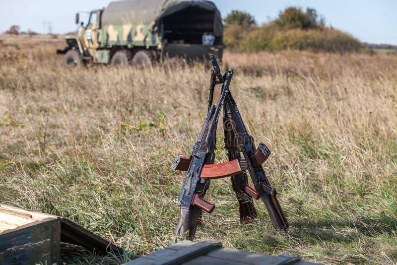 Los rifles de asalto doblaron en la forma de una choza en el campo de batalla imagen de archivo libre de regalías