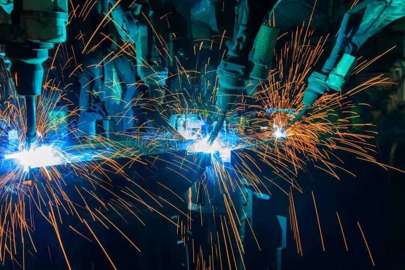 Los robots industriales están soldando con autógena combinando la parte automotriz en fábrica del coche imágenes de archivo libres de regalías