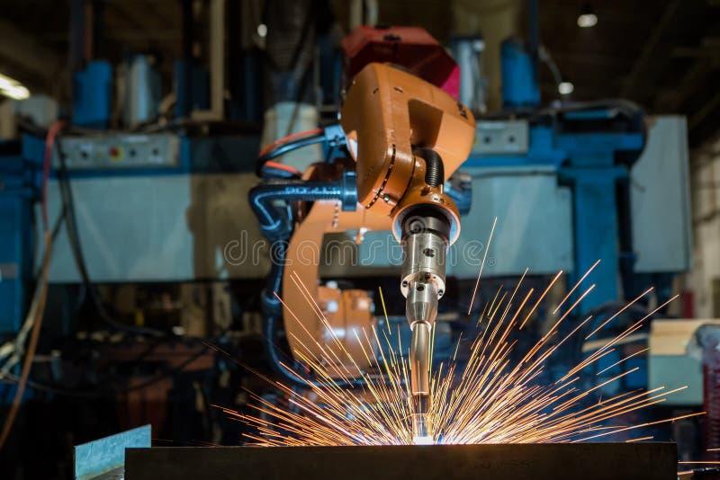 Los robots industriales están soldando con autógena la pieza de la asamblea en fábrica del coche fotografía de archivo