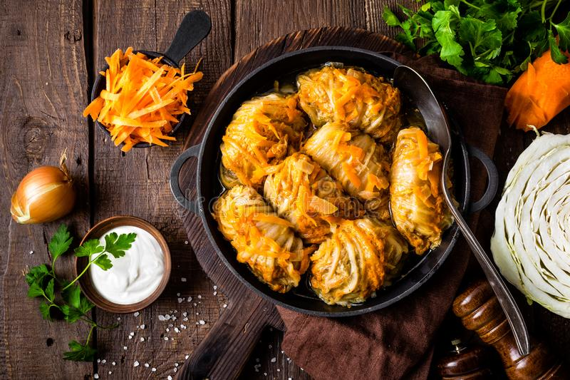 Los rollos de la col guisaron con la carne y las verduras en cacerola en el fondo de madera oscuro, visión superior foto de archivo