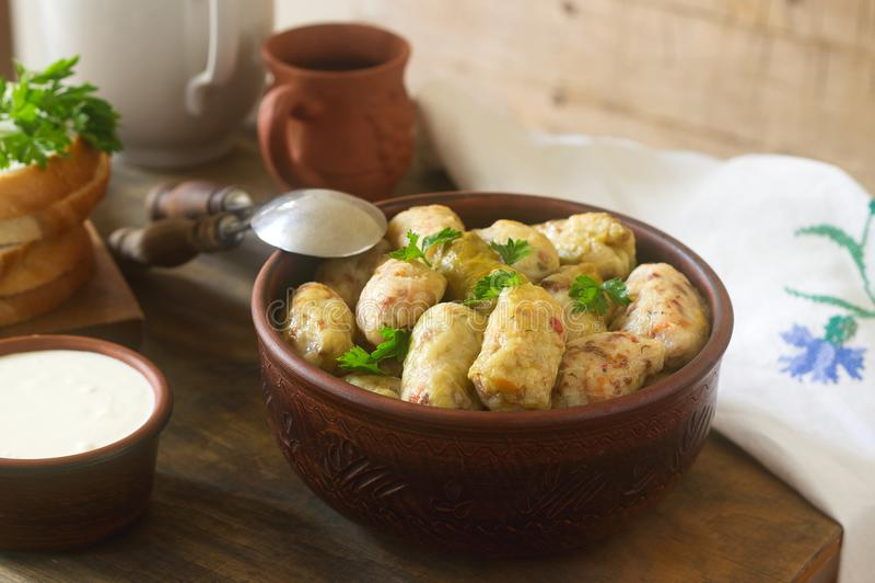 Los rollos de la col sirvieron con crema agria, pan y vino Dolma, sarma, sarmale, golubtsy o golabki foto de archivo