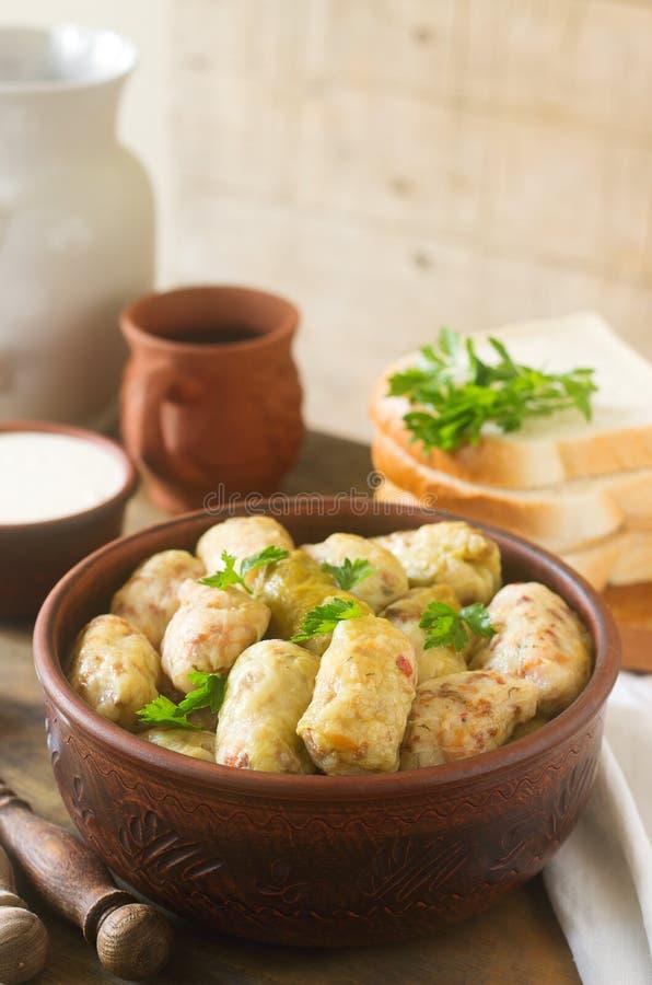 Los rollos de la col sirvieron con crema agria, pan y vino Dolma, sarma, sarmale, golubtsy o golabki imágenes de archivo libres de regalías