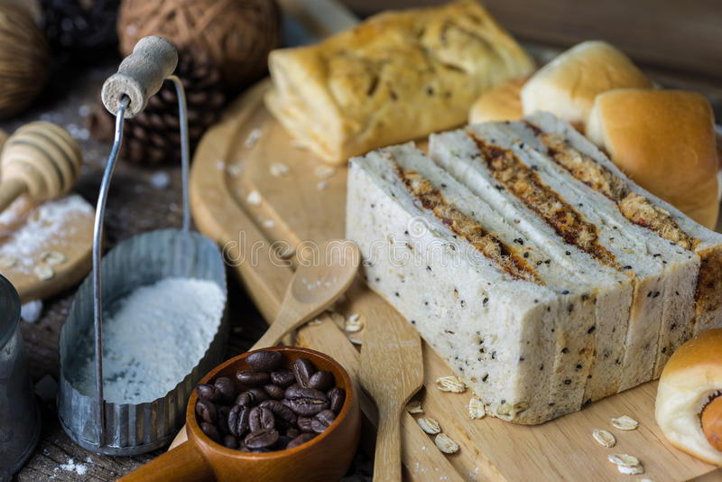 Los rollos de pan recientemente cocidos del surtido sacaron el polvo ligeramente con la harina en una tabla de madera imagenes de archivo