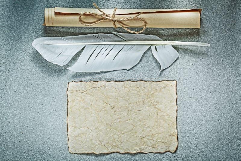 Los rollos de papel de la hoja del vintage plume en fondo gris imágenes de archivo libres de regalías