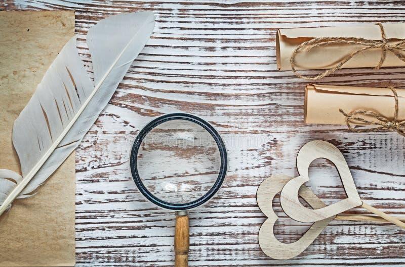 Los rollos del papel de la hoja del vintage plume la lupa de madera de los corazones en la madera fotos de archivo libres de regalías