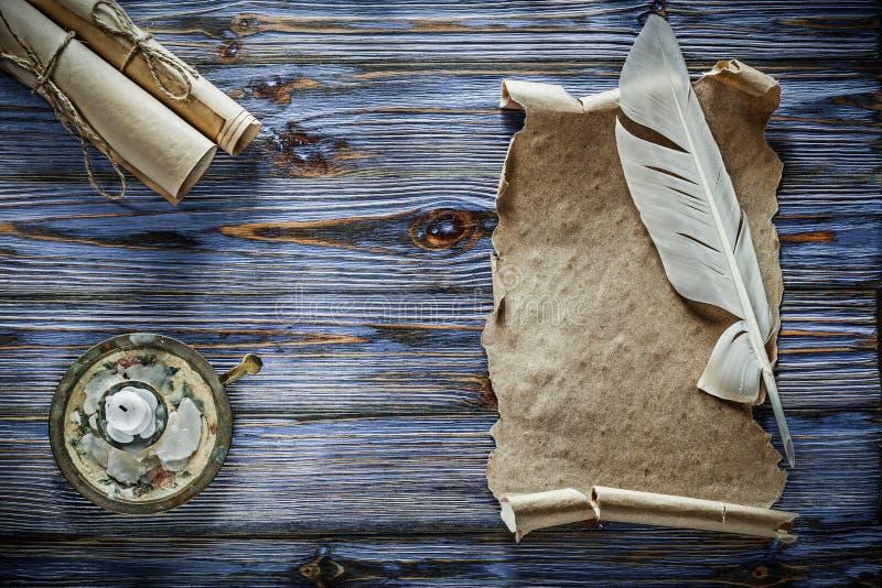 Los rollos del papel del vintage plume el candelero en fondo de madera azul foto de archivo libre de regalías