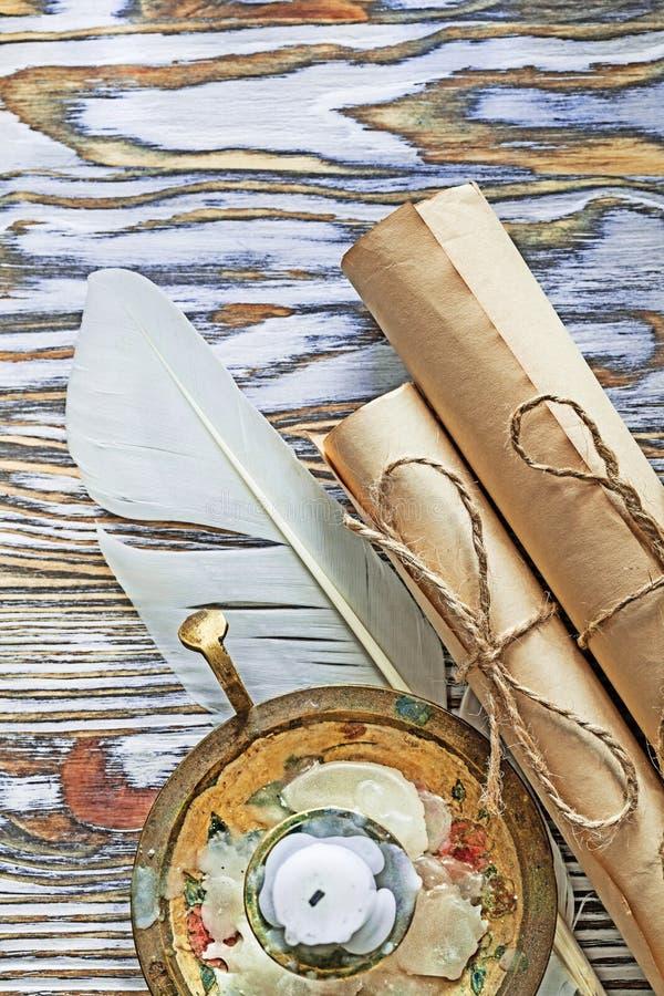 Los rollos del papel del vintage plume la vela del candelero en el tablero de madera imagenes de archivo
