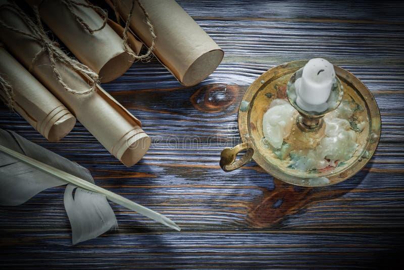 Los rollos del papel del vintage plume la vela de la palmatoria en verraco de madera azul imágenes de archivo libres de regalías